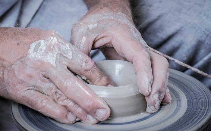 Mit Werkstätten zur Service Public Revolution: Eine Hand formt nassen Lehm auf einer Töpferscheibe