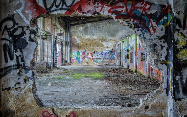 Leerstand in der Kleinstadt: Eine besprühte Wand mit Loch in der Mitte