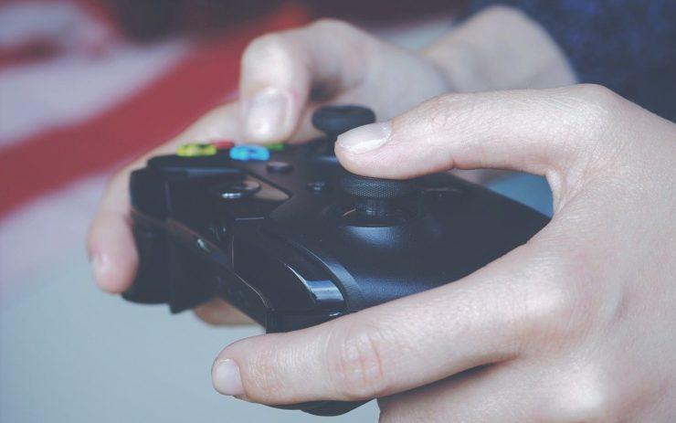 Spiele gibt es bei Gamestop: Eine Hand spielt mit einem Controller ein Videospiel