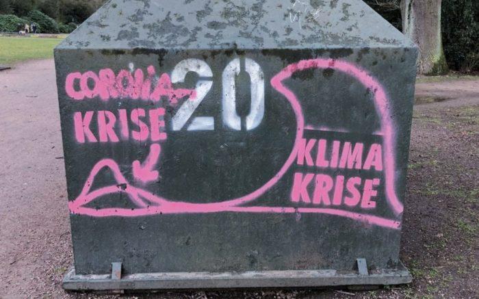 """Graffiti: Eine große Welle mit der Aufschrift """"Klima-Krise"""" überrollt eine kleinere Welle mit der Aufschrift Corona-Krise"""