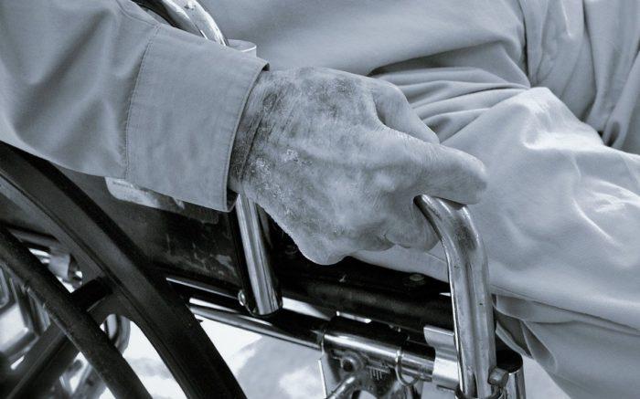 Ein Mensch sitzt im Rollstuhl in der Pflege