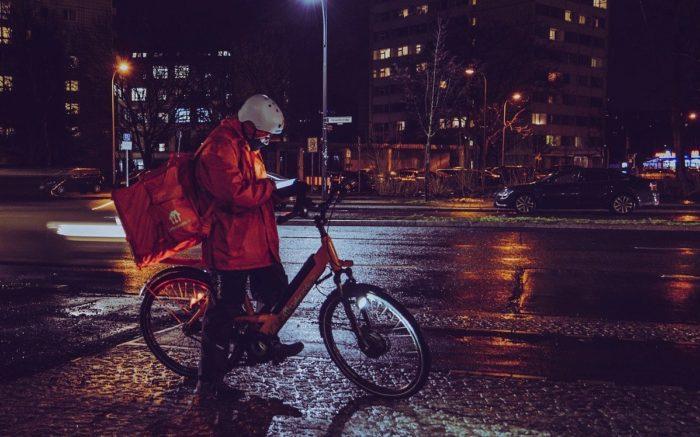 Granzgängerin: Ein:e Lieferando-Fahrer:in steht an einer Straße und schaut auf das Handy.