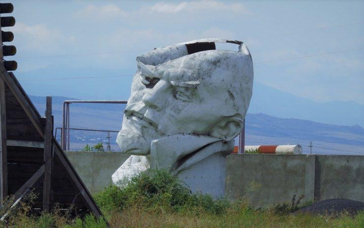 In einer heruntergekommen Landschaft steht eine kaputte Lenin Statur. Wiederaufbau als Lösung der Klimakrise?