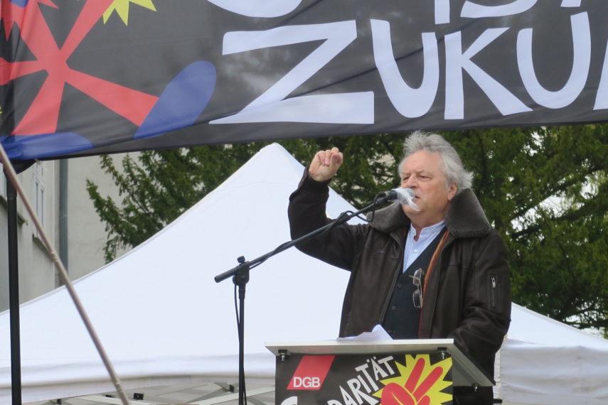 Klaus Dörre hebt am Rednerpult die Hand