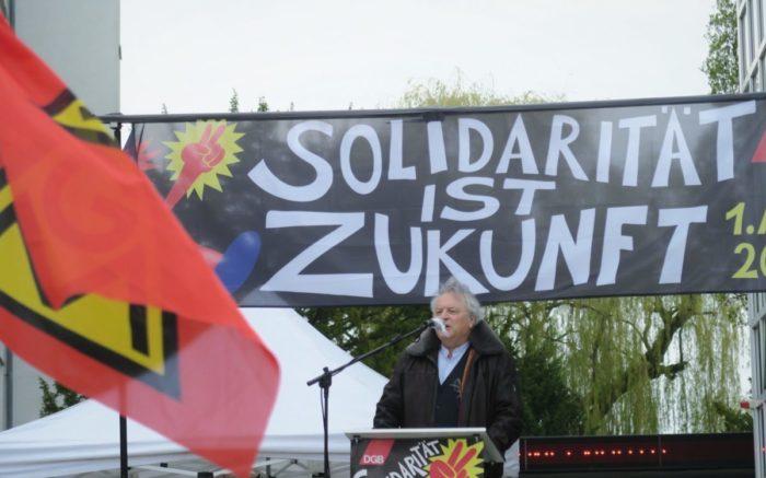 Klaus Dörre am Rednerpult vor dem Transparent Solidarität ist Zukunft