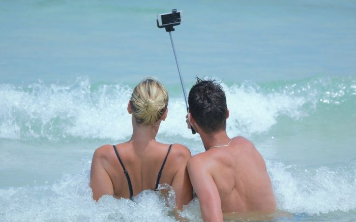 Influencer fotografieren sich mit einem Selfie-Stick am Strand in den Wellen