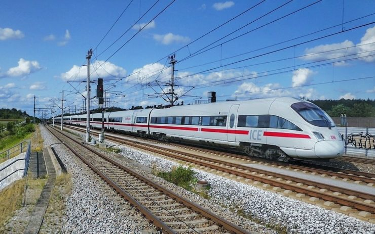 In den Neunzigern wurde die Deutsche Bahn privatisiert - Ist das der Neoliberalismus? Ein ICE-Zug fährt bei schönem Wetter über Gleise.