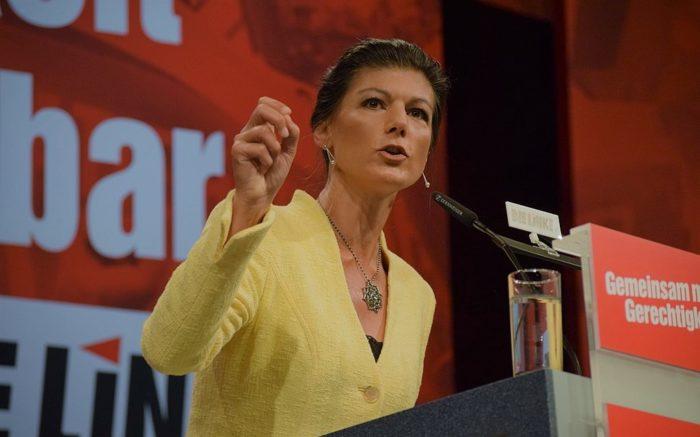Sahra Wagenknecht hält eine Rede vor einem Pult mit Werbung für DIE LINKE
