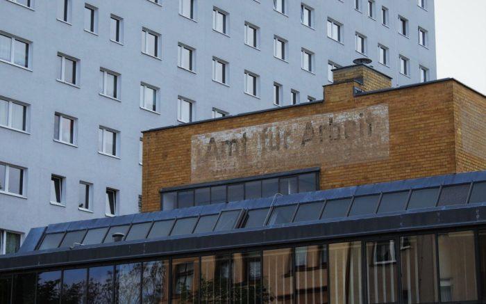 """Ein altes Gebäude mit der verblassenden Aufschrift """"Amt für Arbeit"""" steht vor einem Plattenbau"""