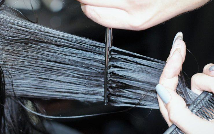 Eine Schere schneidet viel von den nassen langen Haare einer Person ab. Auch das hat einen Preis