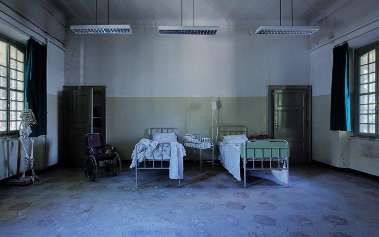 Eine triste Pflege-Einrichtung mit zwei Betten und kaputten Wänden