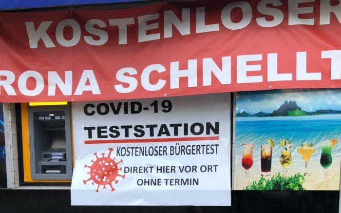 Beispiel für viele Corona-Testzentren: Ein Zentrum in Berlin-Wedding wirbt mit einem großen roten Schild und einer schlecht aufgeklebten Folie. Daneben werden Cocktails am Meer dargestellt. Außerdem befindet sich ein Geldautomat an der Fassade.