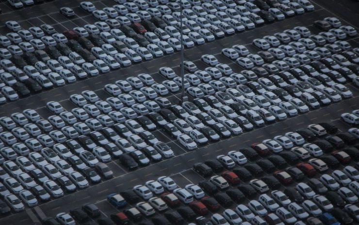 Die Klimakrise wird auch durch das Auto ausgelöst: Auf einem Parkplatz stehen viele weiße Autos, nur wenige Plätze sind frei.
