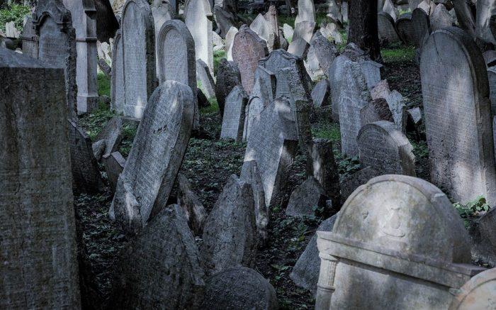 Alte Grabsteine, kreuz und quer übereinander stehen