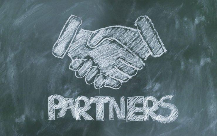 """Auf einer Tafel ist mit Kreide ein Handschlag gezeichnet. Darunter steht """"Partners""""."""
