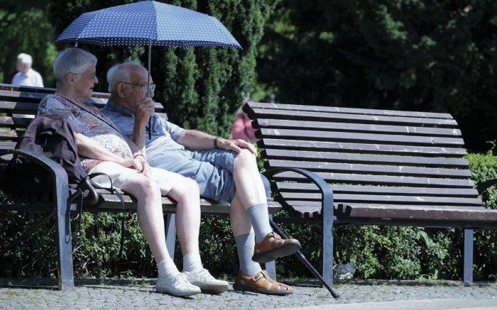 Zwei Renter:innen sitzen auf einer Bank im Park, neben ihnen ist noch eine freie Bank.