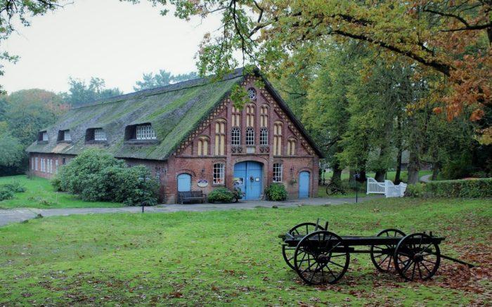 Ein Bauernhaus mit einem Kutschenwagen davor