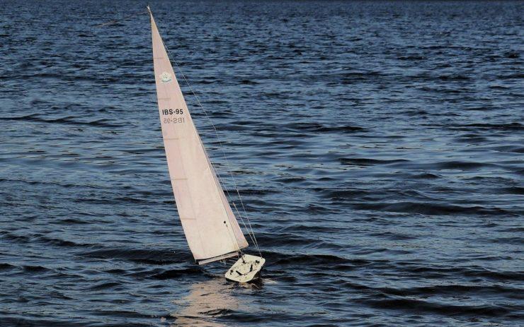 Ein Modell-Segelboot segelt über stilles Gewässer